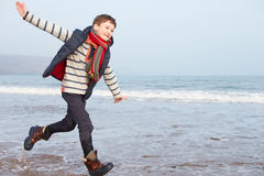 Young Boy Running Along Winter Beach Royalty Free Stock Photos
