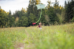 Young boy running away from the camera  flying a kite Stock Image
