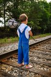 A Young Boy Running Away. A runaway boy standing on a train track Royalty Free Stock Images