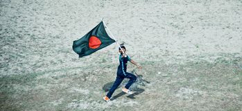 Young boy running with a Bangladeshi national flag. A young boy running with a red green national flag of Bangladesh isolated unique editorial photo stock images