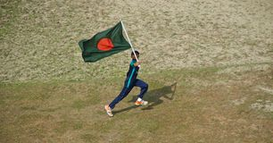 Young boy running with a Bangladeshi national flag. A young boy running with a red green national flag of Bangladesh isolated unique editorial photo royalty free stock photos