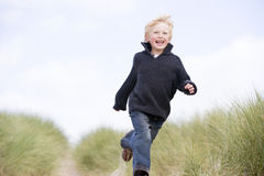 Young boy running on beach royalty free stock photos