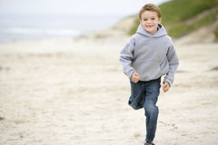 Young boy running on beach. Smiling Stock Photos