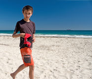 Young boy running on beach. Young eurasian boy running on beach with sea in background Royalty Free Stock Photo
