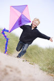 Young boy running on beach with kite smiling. At camera Royalty Free Stock Images