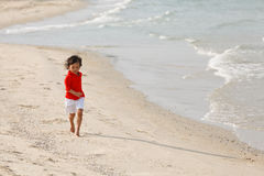 Young boy running on beach. Little boy in red shirt runing on beach Royalty Free Stock Images