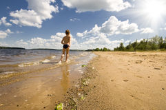 Young boy running at the beautiful beach. On river under sky Royalty Free Stock Image