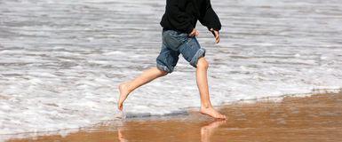 Young Boy Running Feet Ocean Beach Surf Crashing Sea Foam Stock Image