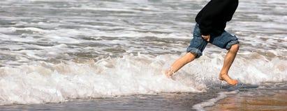 Young Boy Running Feet Ocean Beach Surf Crashing Sea Foam. Panoramic shot of boy playing in the ocean surf Stock Photo