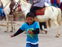 Young Boy Running at a Festival in Ecuador. Young child is playing and running in the street at a festival in Banos Ecuador. He has an expressive face as he Stock Images