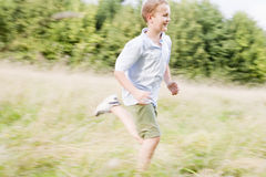 Young boy running in a field smiling.  Royalty Free Stock Photography