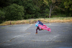 A young boy running while holding the  American Flag showing patriotism for his own country, Unites States Stock Photography
