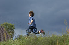Young Boy Running Home. Young boy is running through the meadow for the shelter of his home with rain storm approaching Stock Photo