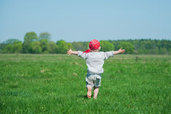 Young boy running on the meadow. Feel freedom on the green meadow Stock Images