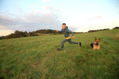 Young boy running on the meadow at sunset. Happy, little boy running on the green, mountain meadow at sunset with his faithful a large dog - German Shepherd Stock Photo
