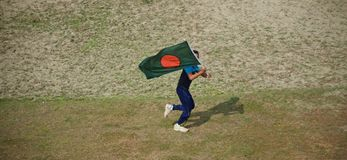 Young boy running with a Bangladeshi flag. A young boy running with a national flag of Bangladesh around a field unique photo royalty free stock photos