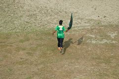 Young boy running with a Bangladeshi flag. A young boy running with a national flag of Bangladesh around a field unique photo royalty free stock photo