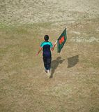 Young boy running with a Bangladeshi flag. A young boy running with a national flag of Bangladesh around a field unique photo stock photos