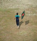 Young boy running with a Bangladeshi flag. A young boy running with a national flag of Bangladesh around a field unique photo stock photos
