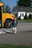 Young boy running off the school bus smiling. Young boy running off the school bus after his first day of school Royalty Free Stock Photography