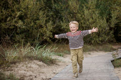 Young boy running with open arms Stock Photo