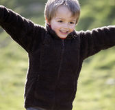 Young boy running outdoors. Young boy smiling and running with arms outstretched outdoors Stock Images