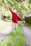 Young boy running on a path outdoors smiling Stock Images