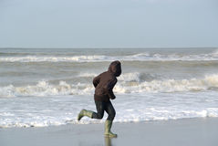 Young boy running at the sea. Young kid running on the beach. Motion blur at feet Stock Photos