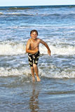 Young boy running through the water at the beach. Happy young boy running through the water at the beach Stock Photo