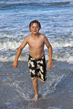 Young boy running through the water at the beach Royalty Free Stock Photo