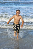Young boy running through the water. Happy young boy running through the water at the beach Stock Photography
