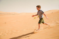 Young boy runs down in desert sand Stock Photo