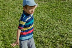 Young boy runs in a green field. Cute child running across park outdoors grass. Young boy runs in a green field. Cute child running across park outdoors grass Stock Photos
