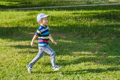 Young boy runs in a green field. Cute child running across park outdoors grass. Smiling stock photography