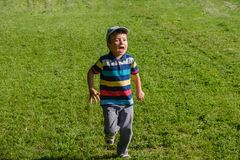 Young boy runs in a green field. Cute child running across park outdoors grass. Young boy runs in a green field. Cute child running across park outdoors grass Royalty Free Stock Image