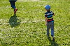 Young boy runs in a green field. Cute child running across park outdoors grass. Young boy runs with his mother in a green field. Cute child running across park royalty free stock photography