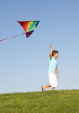 Young boy runs with kite through field Stock Photo