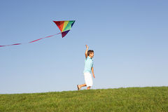 Young boy runs with kite through field. In the sun Royalty Free Stock Image