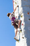 Young Boy's Determination. Young boy determination while climbing up an artificial rock wall stock image