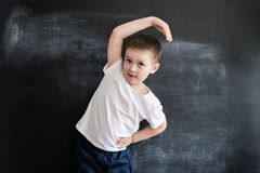 Young boy`s doing athletic exersices near blackboard. Young athlete. Creative design concept for 2019 calendar. Young boy`s doing athletic exersices near stock photo