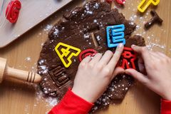 Young boy`s hands cut cookies from raw chocolate dough on a wooden table with colorful letters. Cooking traditional Easter royalty free stock image
