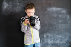 Young boy`s shooting with photo camera near blackboard. Young photographer. Creative design concept for 2019 calendar. Young boy`s shooting with photo camera royalty free stock image