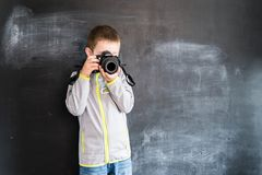 Young boy`s shooting with photo camera near blackboard. Young photographer. Creative design concept for 2019 calendar. Young boy`s shooting with photo camera royalty free stock images