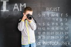 Young boy`s shooting with photo camera near blackboard. Young photographer. Creative design concept for 2019 calendar. August stock images