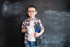 Young boy`s standing with keyboard and network wire near blackboard. Young programmer or system administrator. Creative design co stock photos