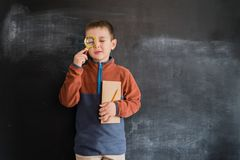 Young boy`s standing with magnifying glass and notebook in his hands near blackboard. Young detective. Creative design. Concept for 2019 calendar stock photography