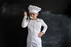 Young boy`s standing near blackboard checking soup. Young chef boy. Creative design concept for 2019 calendar. Young boy`s standing near blackboard checking royalty free stock photo