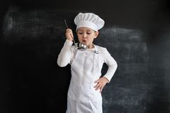 Young boy`s standing near blackboard checking soup. Young chef boy. Creative design concept for 2019 calendar. Young boy`s standing near blackboard checking royalty free stock image