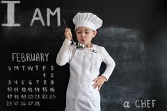 Young boy`s standing near blackboard checking soup. Young chef boy. Creative design concept for 2019 calendar. February.  stock image