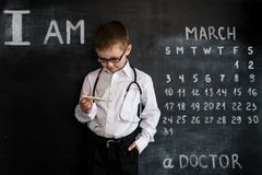 Young boy`s standing near blackboard checking thermometer. Young doctor. Creative design concept for 2019 calendar. March royalty free stock photo